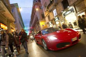 A Ferrari drives down Rome's fashionable Via del Corso shopping street on Dec. 9.