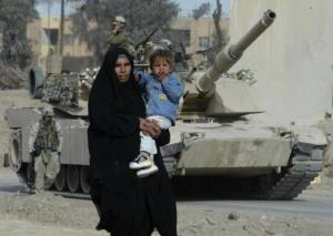 An Iraqi woman carries her son in front of an US Marines Abrams tank in Fallujah.