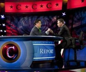 Stephen Colbert, center, and John Stewart, right, hold hands during The Colbert Report, as Trevor Potter looks on, Jan. 12, 2012, in New York.