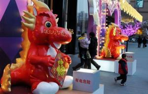 Shoppers walk past a Chinese Spring Festival 'Year of the Dragon' display at a shopping center in Beijing on January 20, 2012.