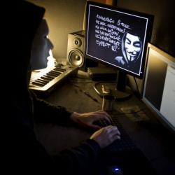 A masked hacker, part of the Anonymous group, hacks the French presidential Elysee Palace website on January 20, 2012 near the eastern city of Lyon.