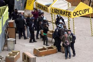 NYPD officers arrest a photojournalist, bottom right, as they clear out Occupy Wall Street activists in a private park next to Duarte Square on November 15, 2011, in New York City.