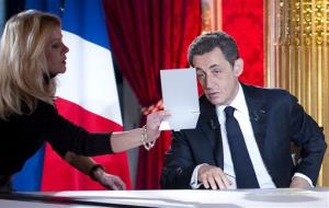 Sarkozy looks in a mirror shortly before an hour-long interview shown on French TV Sunday night.