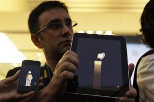 Apple computer fans hold their iPhone and iPad displaying candle graphics during a candle light vigil to pay tribute to Steve Jobs, the Apple founder and former CEO, at an Apple Store in the Ginza shopping district in Tokyo Thursday, Oct. 6, 2011. Jobs died on Wednesday at the age...