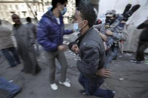 Egyptian protestors carry an injured youth to a filed hospital during clashes with security forces near the Interior Ministry in Cairo, Egypt, Saturday, Feb. 4, 2012.