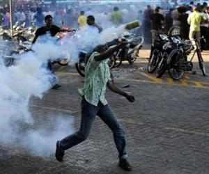 An anti-government protester throws back a teargas cannister to police in the capital island Male on February 8, 2012.