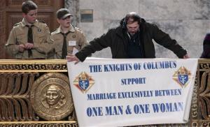 An opponent places a sign against gay marriage in the Capitol rotunda before yesterday's vote.