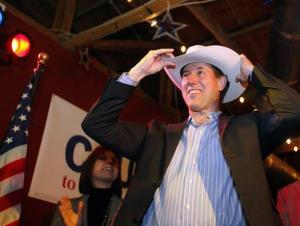 Rick Santorum puts on a cowboy hat after meeting with supporters at a rally in Texas yesterday.