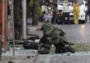 A Thai Explosive Ordnance Disposal (EOD) official examines a backpack that was left on the bomb site by a suspected bomber in Bangkok, Thailand Tuesday, Feb. 14, 2012.