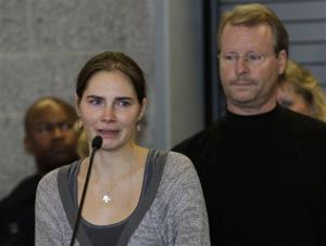 Amanda Knox talks to reporters as her father, Curt Knox, right, stands behind her Tuesday, Oct. 4, 2011, in Seattle.