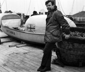In this Jan. 3, 1969, file photo, John Fairfax stands beside his 22-foot rowing boat, Britannia, at King George V Dock in London, prior to sailing to the Canary Islands.