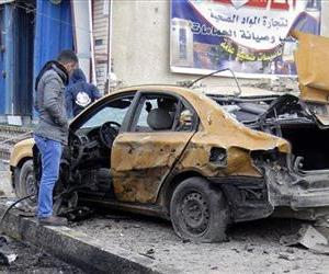 Ahmed Ali inspects his destroyed car after a car bomb explosion in Baghdad, Iraq, Thursday, Feb. 23, 2012.