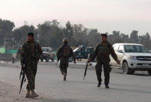 Afghan National Army soldiers block a road near the site of a suicide attack in Jalalabad today.