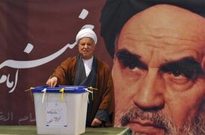 In front of a portrait of late Iranian leader Ayatollah Khomeini, former President Akbar Hashemi Rafsanjani casts his ballot for the parliamentary elections at a polling station in Tehran, March 2, 2012.