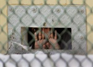 In this Dec. 4, 2006 file photo,  detainee shields his face as he peers out through the so-called bean hole which is used to pass food and other items into detainee cells.