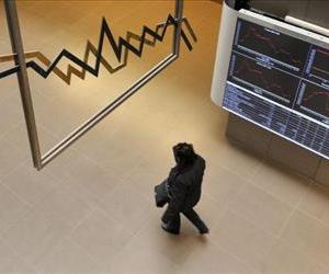 A woman walks under an electronic  index display at the Athens stock exchange on March 9, 2012.