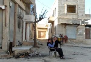 Armed Syrian men sit in a street in the city of Rastan, near the flashpoint city of Homs, on March 9, 2012 which has been bombed by Syrian forces intermittently since February 5. AFP PHOTO/STR