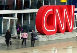 FFILE- This Jan. 17, 2001 file photo shows pedestrians entering CNN Center, the headquarters for CNN,  in downtown Atlanta. The latest rough patch for CNN illustrates the two contradictions at the network's heart. In a brutal time for the news business, CNN is one of the few media organizations thriving...
