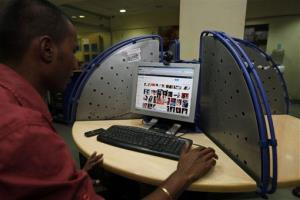 An Indian man views a Google page at an Internet cafe in Hyderabad.