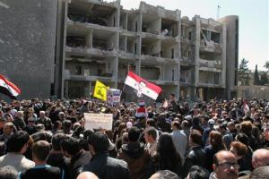 Thousands of people wave Syrian flags during a silent march in front of a damaged government building in Damascus, Syria, Sunday, March 18, 2012.