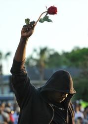 Wearing a hoodie and holding a rose, a person attends a rally for Trayvon Martin yesterday.