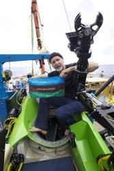 James Cameron holds the National Geographic Society flag after he successfully completed the first ever solo dive to the Mariana Trench Monday March 26, 2012.