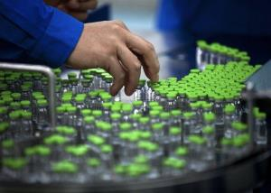 In this 2011 photo, a worker inspects labels on vials containing H5N1 flu vaccine during production at the Beijing-based drug maker Sinovac Biotech Ltd. in Beijing.