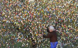 In this March 21, 2012 file picture Volker Kraft decorates a tree with 10,000 Easter eggs in the garden of the retired couple Christa and Volker Kraft in Saalfeld, Germany.