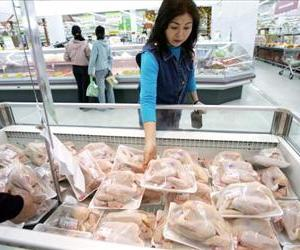 A woman picks out a chicken at a grocery store in this file photo.