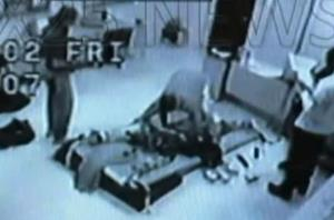 Andre McCollins is restrained and shocked in this frame grab from a 2002 video.