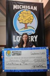 Amanda Clayton holds her $1 million lottery check.