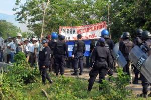 Riot squad officers stand guard as rural workers  vacate a plot of land they had occupied earlier in the day in San Manuel, north of Tegucigalpa.
