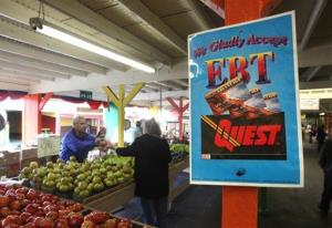 A sign announcing the acceptance of Electronic Benefit Transfer cards is seen at a farmers market in Roseville, Calif.