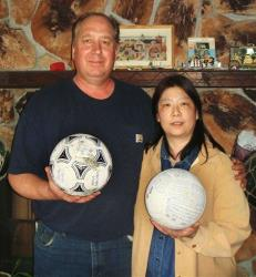 David and Yumi Baxter hold a soccer ball and a volleyball which floated across the Pacific to Alaska after the Japanese tsunami.