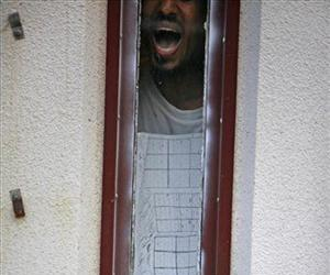 A detainee stands at his cell window yelling after seeing a group of journalists who were visiting Camp 5 maximum-security detention facility in Guantanamo Bay, May 13, 2009.