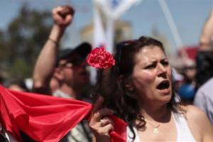 A Greek Communist party supporters holds a red carnation during a May Day protest on Tuesday May 1, 2012, in the Aspropyrgos industrial area, outside Athens.