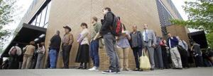 In this April 24, 2012 file photo, job seekers wait in line during a job fair, In Portland, Ore.