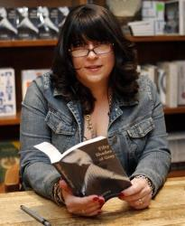 Author EL James holds a copy of her book 50 Shades of Grey at a book signing in Coral Gables, Fla., Sunday, April 29, 2012.