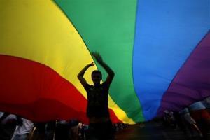 A gay rights activist dances under a rainbow flag.