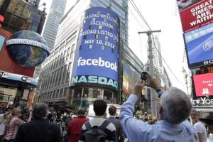 A man stops to photograph Nasdaq in Times Square as Facebook has its IPO, Friday, May 18, 2012, in New York.