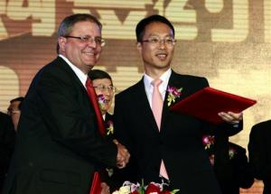 Gerry Lopez, CEO of AMC Entertainment Holdings, left, shakes hands with Zhang Lin, Vice President of Wanda during a signing ceremony in Beijing, China, Monday, May 21, 2012.