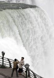 In this April 11 photo, tourists take photographs at the American Falls in Niagara Falls, NY.
