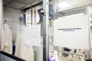 A sign warns visitors not to tap the glass of an above-ground version of the laboratory to be opened nearly 4,900 feet beneath the earth in Lead, S.D. Tuesday, May 29, 2012. The lab's experiments will include the world's most sensitive dark-matter detector. Scientists say that the Sanford...