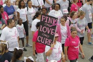 In this April 14, 2012, photo walkers show colorful signs and attire during the Susan G. Komen Race for the Cure in Fort Worth, Texas.