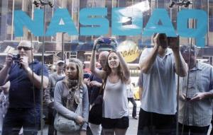 Bystanders watch through the Nasdaq windows as Facebook shares began trading on May 18th, 2012.