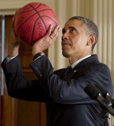 US President Barack Obama pretends to shoot a basketball given to him by the University of Kentucky men's basketball team during an event celebrating their 2012 NCAA championship in the East Room of the White House in Washington, DC, on May 4, 2012. AFP PHOTO / Saul LOEB