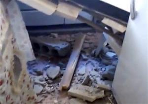 This image made from amateur video released by Shaam News Network shows a destroyed building in Deir el-Zour, Syria.