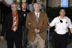 Jerry Sandusky, center, leaves the Centre County Courthouse in custody.