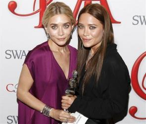 Ashley Olsen, left, and Mary Kate Olsen, designers of The Row, pose backstage after winning Womenswear Designer of the Year at the CFDA Fashion Awards on Monday, June 4, 2012 in New York.