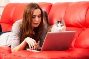 A telecommuter and her cat pause to do some work at home.